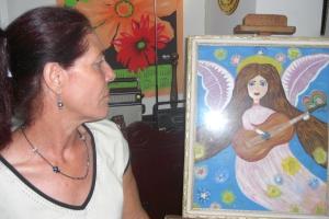 """Grabriela frente a su cuadro  """"El Ángel de la música"""""""